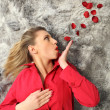 Woman with red coat blowing rose petals — Stock Photo #7803195