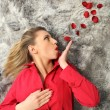 Woman with red coat blowing rose petals — Stock Photo