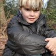 Stock Photo: Young boy sitting in an autumnal forest