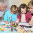 Grandchildren drawing and painting under grandparents' watchful eye — Stok fotoğraf