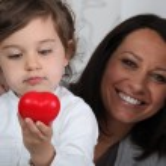 Little girl holding plastic heart — Stock Photo #7804398