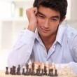 Young man contemplating his next chess move — Stock Photo #7805236