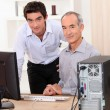 A young man and a senior man behind a computer - Stock Photo
