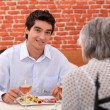 Royalty-Free Stock Photo: Young man having lunch with his grandmother