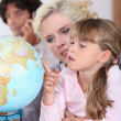 A mother is showing to her daughter some country on a globe, her husband is — Stock Photo