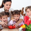 Mother and her daughters making salad — Stock Photo