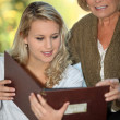 Young woman and her grandmother looking at a photo album - Stock Photo