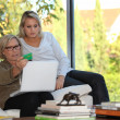 Mother and daughter checking social security online — Stock Photo