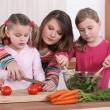 Stock Photo: Mother teaching her daughters how to cook.