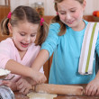 Stock Photo: Two little girls making pancakes