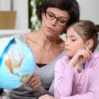 Mother holding a globe and giving explanations to her daughter - Stock fotografie