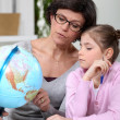 Foto Stock: Mother holding a globe and giving explanations to her daughter