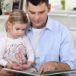 Young father reading his daughter story — Stock Photo