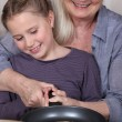 Girl and her granny cooking pancakes - Stock Photo