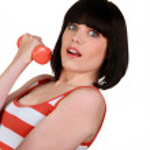 Brunette wearing striped sleeveless top lifting dumbbell — Stock Photo #7805671