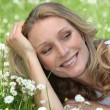 Stock Photo: Closeup of smiling womamongst daisies