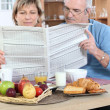 Royalty-Free Stock Photo: Couple reading newspaper at breakfast