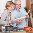 Senior couple reading a recipe book — Stock Photo