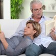 Couple reading on their sofa - Stock Photo