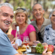 Stock Photo: Older couples enjoying alfresco lunch