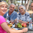 Mature friends eating alfresco — Stock Photo