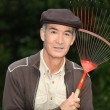 65 years old man wearing brown clothes and holding a rake — Stock Photo