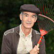 65 years old mwearing brown clothes and holding rake — Stock Photo #7807949