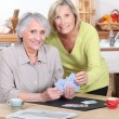 Two mature women playing cards. - Stock Photo