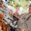 Foto Stock: Wombuying bread from market stall