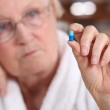 An old woman taking a pill. — Stock Photo #7808208