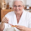 An old woman eating breakfast. — Stock Photo