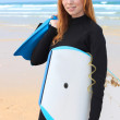Stock Photo: Young female surfer with bodyboard and flippers