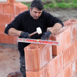 Man erecting a brick wall — Stock Photo