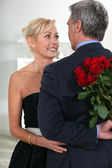 Man surprising his date with roses — Stock Photo