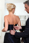Man closing zipper of his wife's dress — Stock Photo