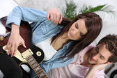 A woman playing guitar and her boyfriend — Stock Photo