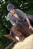 Young man riding a horse — Stock Photo
