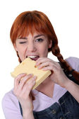 Woman biting into block of cheese — Stok fotoğraf