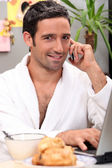 Man working over breakfast — Stock Photo