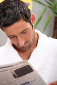 Man reading morning newspaper in kitchen — Stock Photo