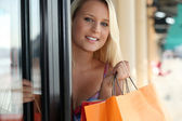 Woman leaving a store with shopping bags — Stock Photo