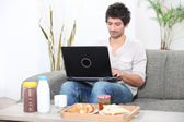 Man looking at his laptop before breakfast — Stock Photo