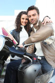 Couple commuting to work on scooter — Stock Photo