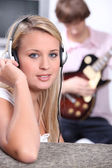 Young woman listening to the music being played by a guitarist sitting behi — Stock Photo