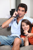 Young couple relaxing on the couch, talking on the telephone and watching t — Stock Photo