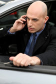 Hombre hablando por su teléfono móvil en su coche — Foto de Stock