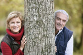 Married couple leaning against tree — Stock Photo