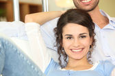 Happy couple sitting on a sofa — Stockfoto
