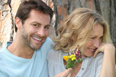 Man offering woman wild flowers — Stock Photo