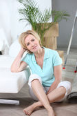 Woman sitting crossed legs on floor of new home — Stock Photo